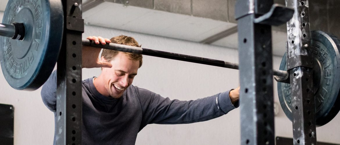 Image of a Strive & Uplift community member preparing to squat at his gym. He is resting his hands wide on the bar, looking down, and smiling broadly.