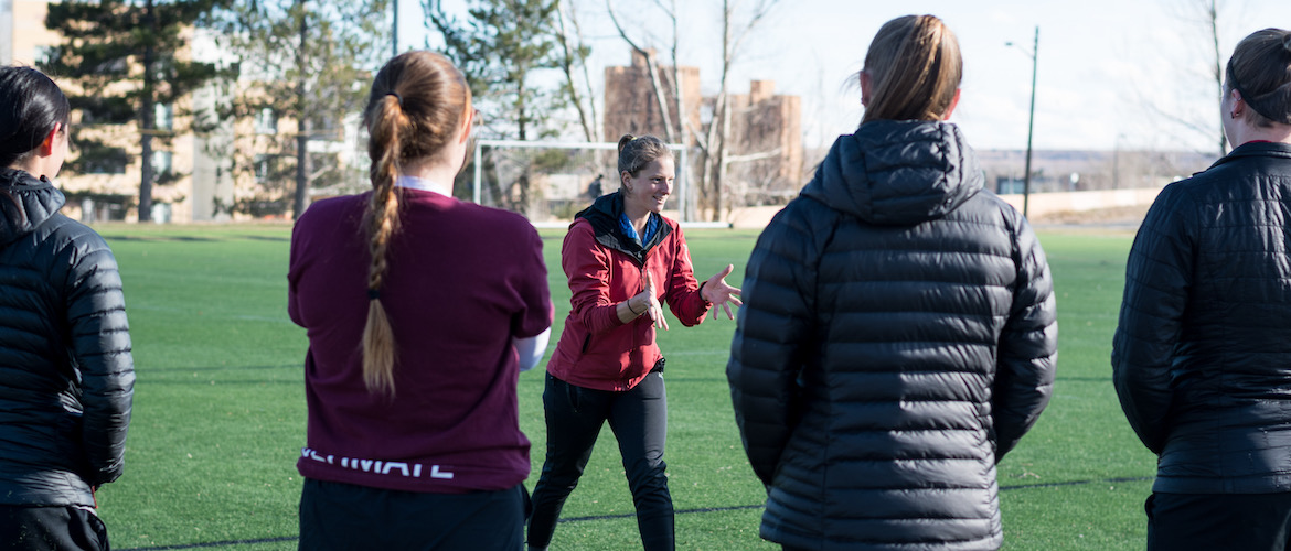 Image of Coach Bert instructing a group of college players on a field in Colorado. Bert is leaning forward, smiling, and gesturing with open hands.