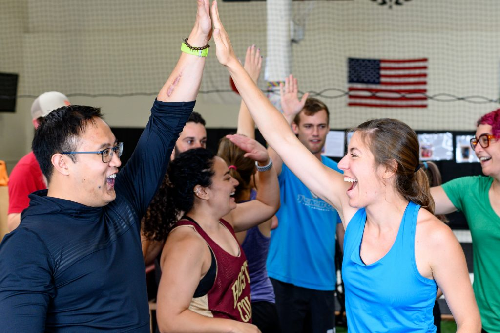 Image of Strive & Uplift community members high fiving each other and smiling.