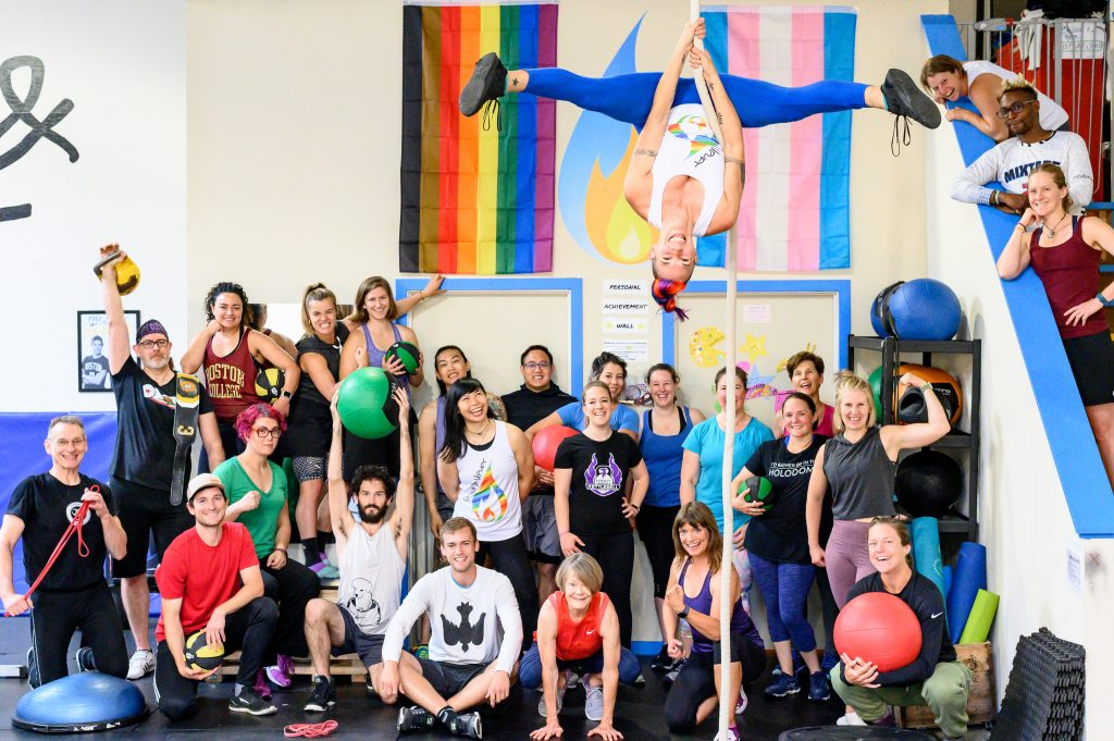 Image of Strive & Uplift community members and coaches posing with gym equipment in front of the Strive & Uplift flame, intersectional pride flag, and transgender pride flag. Ren is in the foreground, inverted on an aerial rope with her legs in side splits.