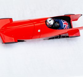 Image of Issy and her partner inside a moving red bobsleigh on a white ice track. Both are wearing their Great Britain suits.
