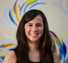 Image of Catherine smiling at the camera. Catherine is a white woman with long brown hair and brown eyes. She is standing in front of a colorful mural.