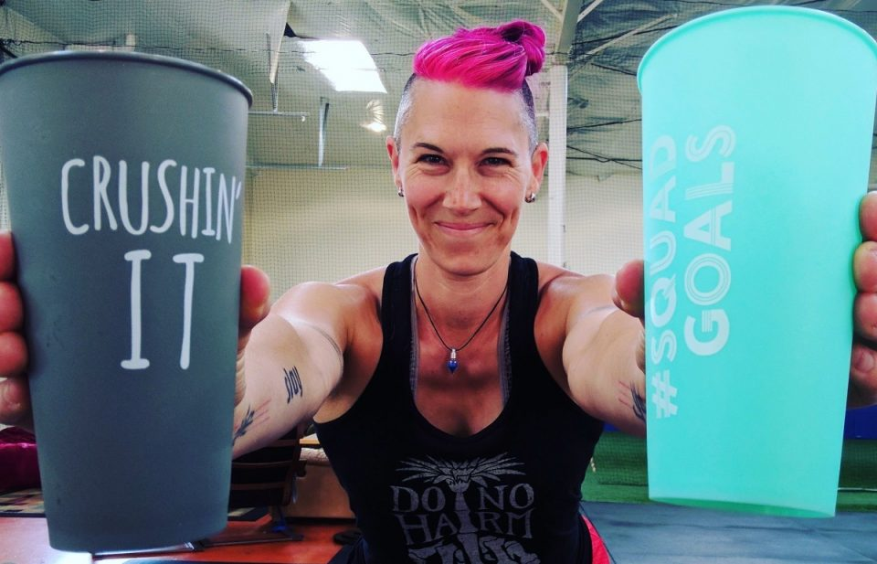 "Image of Ren standing in the gym wearing a black tank top, smirking at the camera while holding forward cups in each hand that say ""Crushin' It"" and ""Squad Goals"". Ren has a fresh pink dye on her bunned up hair."
