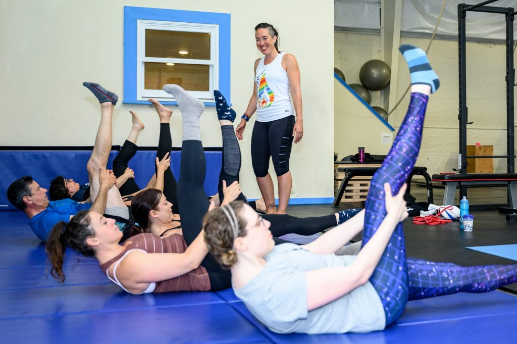 Image of Coach Kira instructing a Mat Pilates class. Six clients are on their backs on thick blue mats while Kira encourages them through the Hamstring Pull exercise.