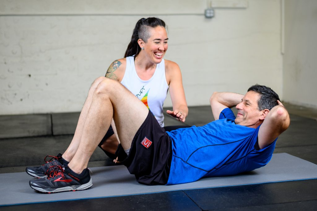 Image of Coach Kira working with a client doing mat Pilates. Both are smiling and laughing as Kira directs the client through the movement.
