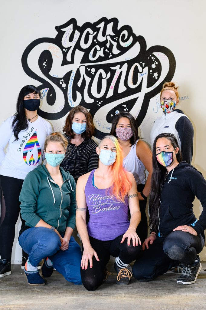 "The seven Strive & Uplift coaches pose wearing masks in front of a mural reading ""You are Strong"""