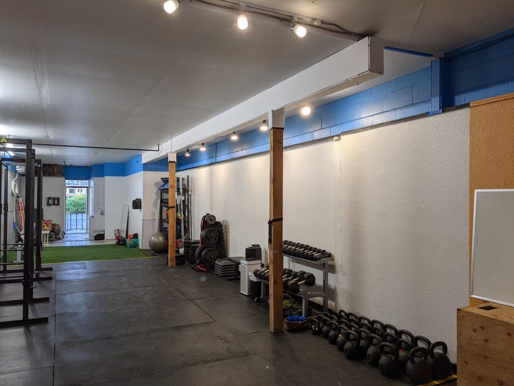 The Ballard gym has two squat racks, barbells and weights, kettlebells, dumbbells, and other functional training equipment. Part of the space has rubber flooring and part is turf.